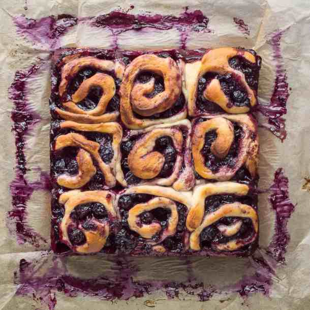 Nine vegan lemon blueberry rolls in a square on a sheet of baking parchment.