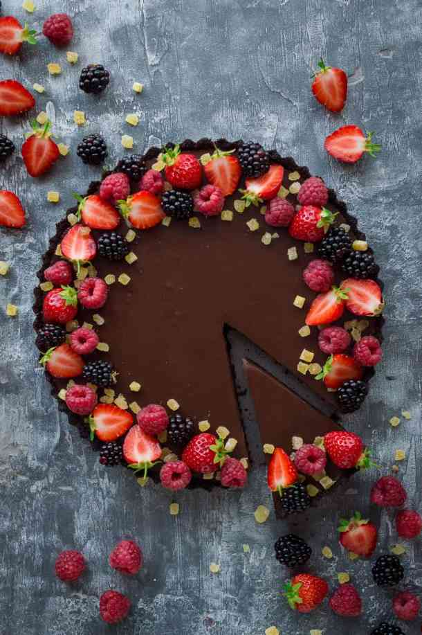 Top down photo of vegan chocolate ginger tart decorated with berries with a slice taken out.