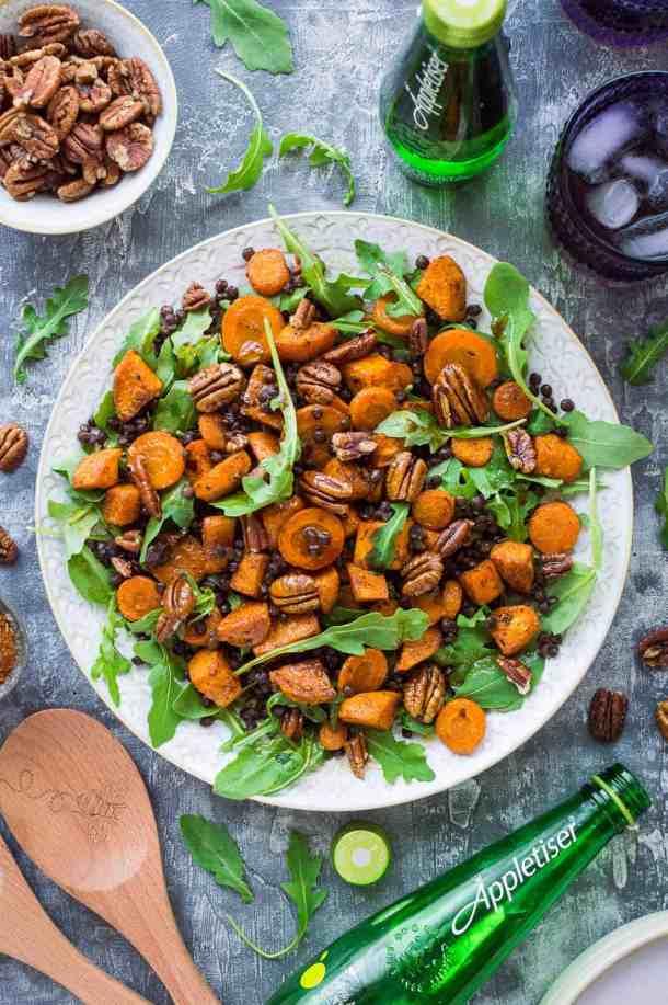 A white platter of roast sweet potato, puy lentil, rocket (arugula) and pecan salad with Appletiser