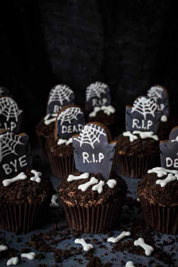 Vegan chocolate cupcakes topped with crushed Oreos, gingerbread tombstones and vegan royal icing bones on a dark background.
