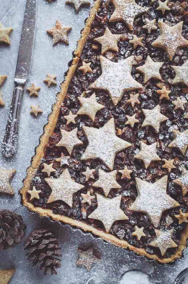 vegan shortbread star topped mince pie tart on agrey background with Christmas decorations.