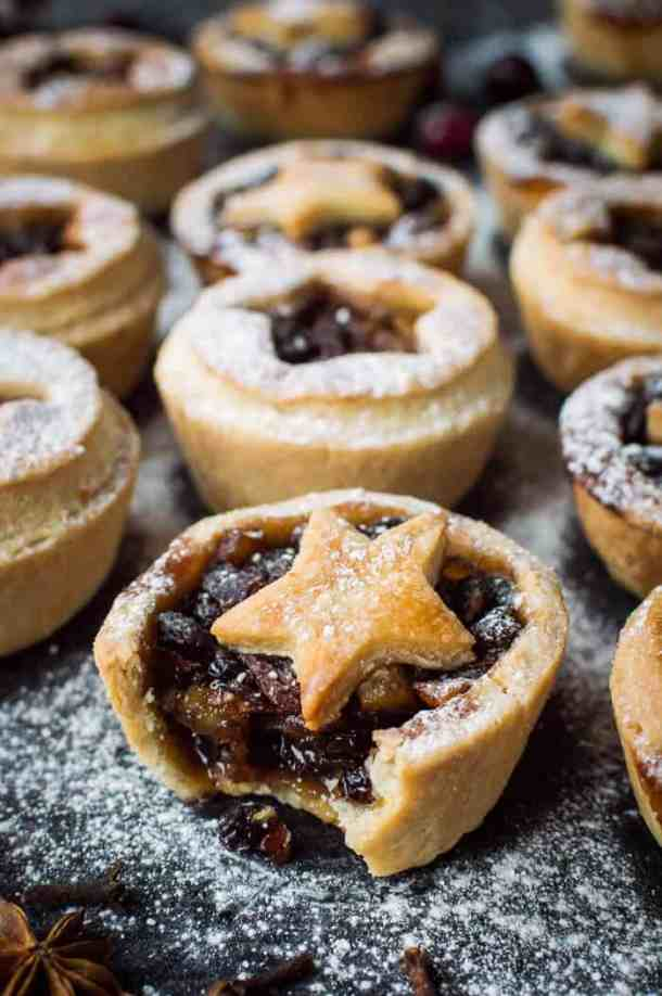 Close up of an icing sugar dusted vegan mince pie with a bite taken out.