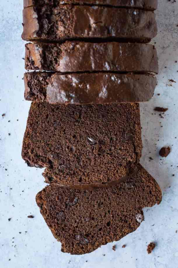 A loaf of sliced vegan double chocolate banana bread on a grey background.