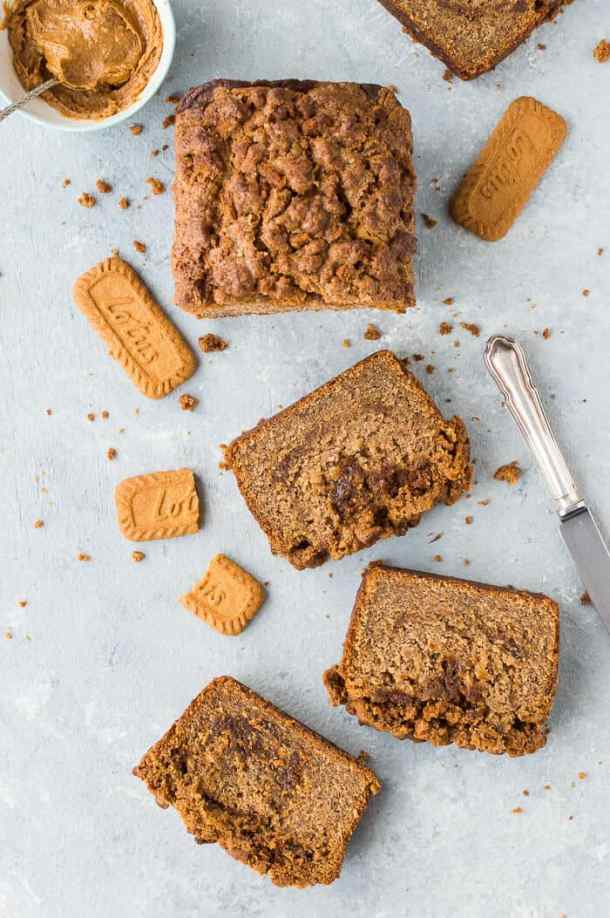 A sliced loaf of vegan biscoff cookie butter banana bread on a grey background with Lotus biscoff biscuits, a bowl of cookie butter and a knife.