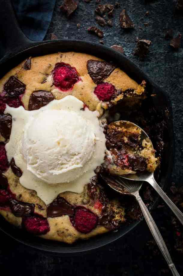 Close up of partially eaten vegan chocolate skillet cookie for two with vanilla ice cream on top and two spoons.