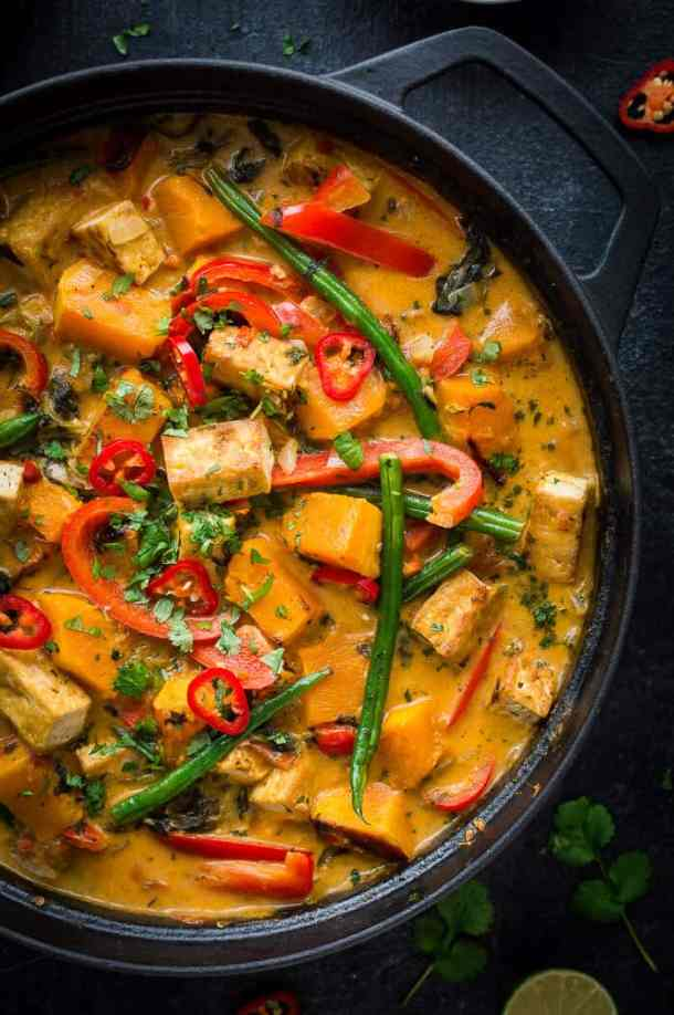 Close up of vegan tofu and vegetable moqueca stew in a black cast iron pan on a black background.