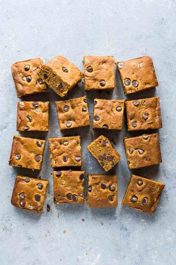 Vegan chocolate chip pumpkin snack cake sliced into squares on a grey background.