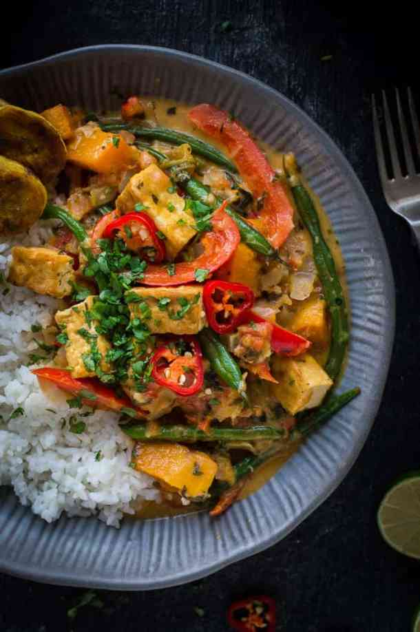 Close up of a grey bowlful of vegan tofu moqueca with white rice and fried plantain.