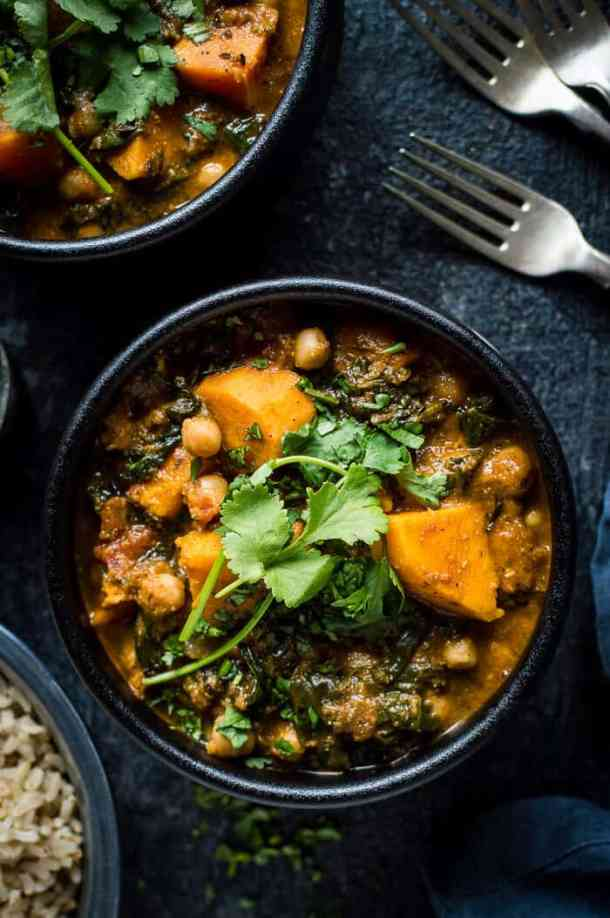 Close up of vegan chickpea, sweet potato and spinach curry in a black bowl on a black background.