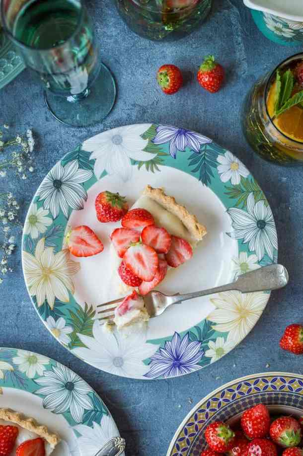 A slice of vegan strawberry tart on a floral plate.