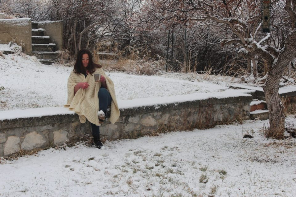 Madeleine Roberg sitting on a stone wall wearing her hand knit Worket™ Shawl.