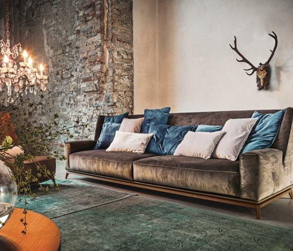 duża sofa, poroże jelenia na ścianie, kamienna ściana