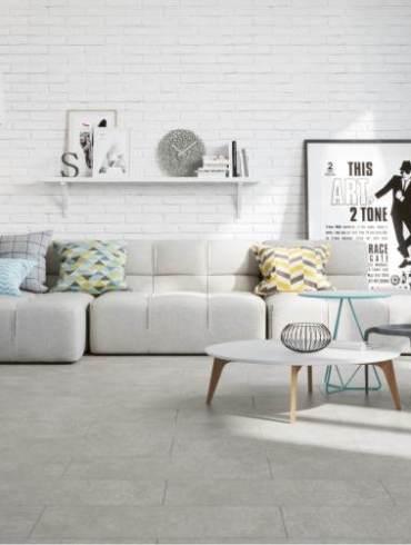 płytki podłogowe imitujące beton, biała cegła na ścianie, sofa, plakat, jasne wnętrze