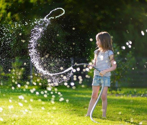 dziewczynka podlewa trawę wężem ogrodowym