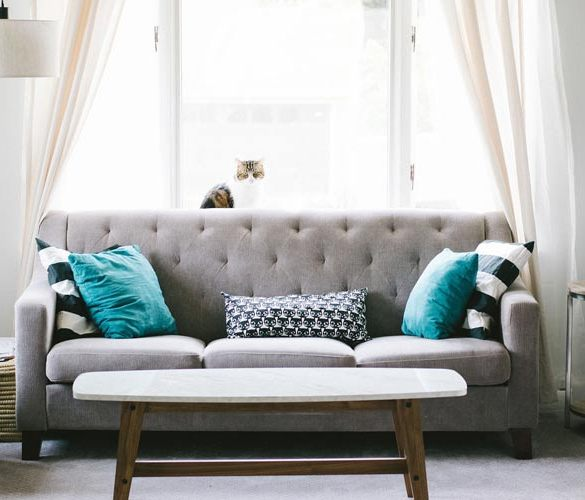 szara sofa dwuosobowa na tle okna