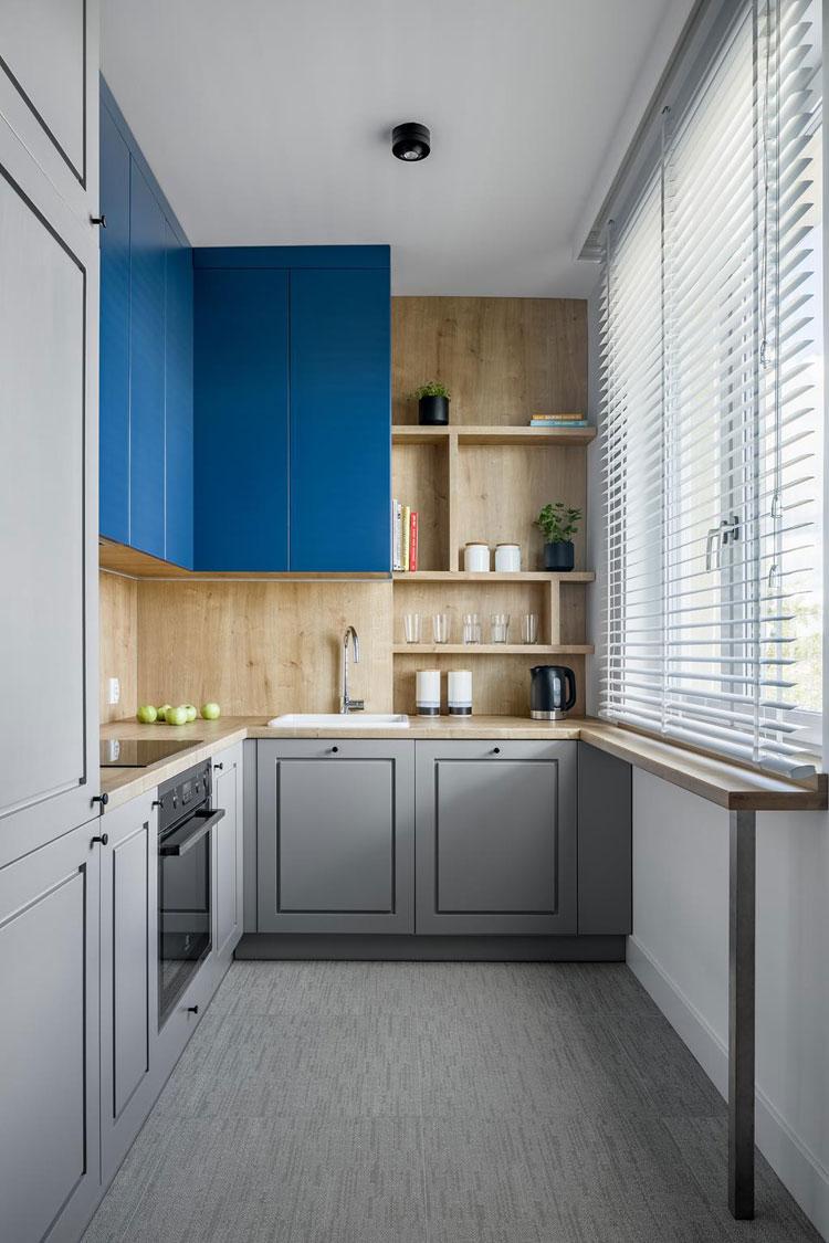 Nieduży aneks kuchenny z szarymi i niebieskimi frontami.