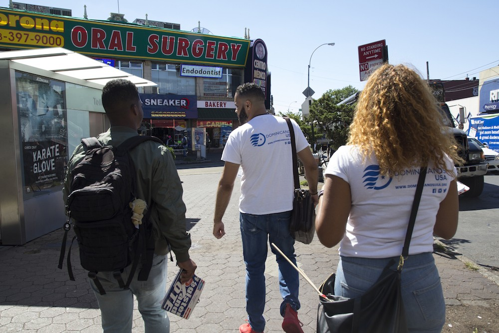 """Canvassers from Dominicanos USA walk down the street in Corona, Queens. """"We get to meet a lot of people and develop those bonds with the community,"""" says Yohan Diaz, left."""