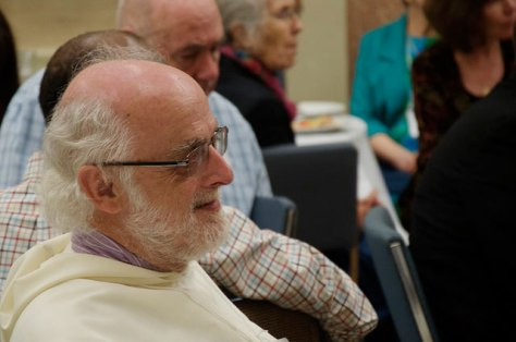A member of a religious order smiles and listens to a conference speaker.