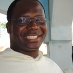 Photo of Roger Houngbedji ,o.p., smiling and wearing a white robe.