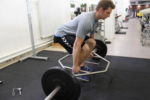 """Ein """"Trap Bar"""" ist großartig um direkt """"durch"""" die Mitte der Beine zu ziehen, statt die Stange an den Beinen entlangzuschleifen."""