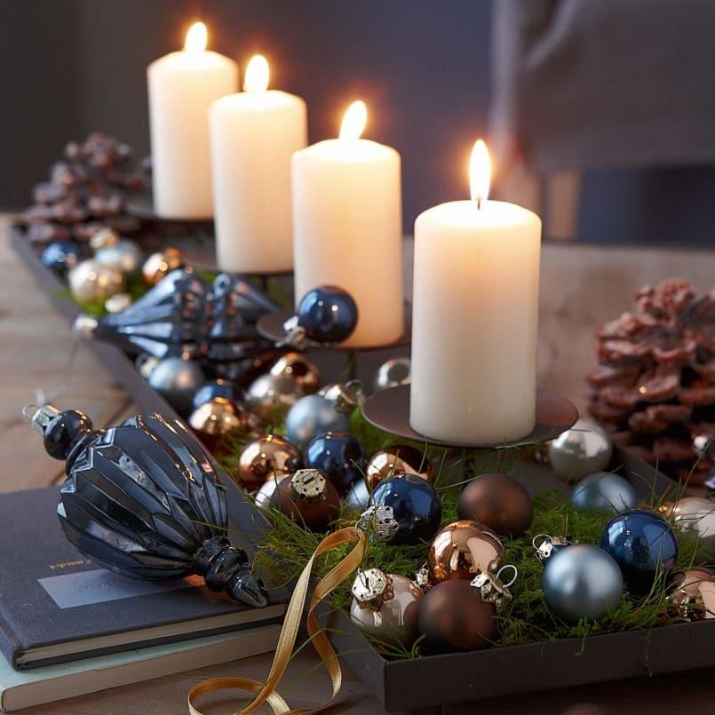 Рождестволық шыршалы ойыншықтармен безендірілген хош иісті шамдар Жаңа жылдық үстелге жақсы қызмет етеді.