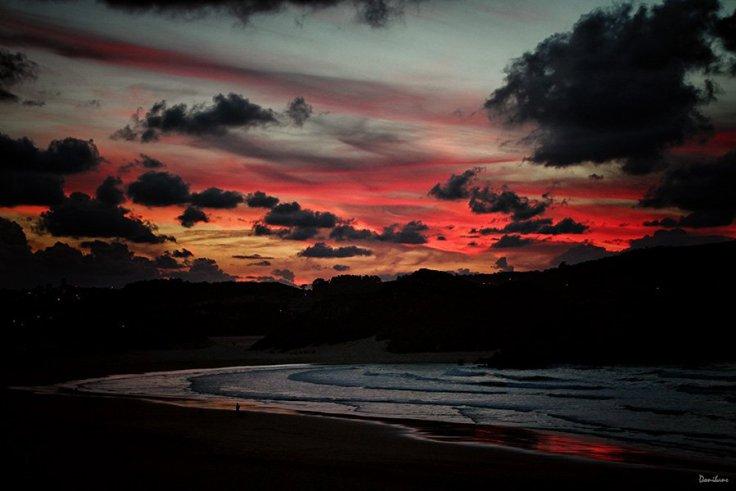 Puesta roja de sol en la playa de Ris en Noja, en Cantabria, por Donibane