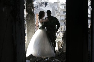 Newly-wed Syrian couple Nada Merhi,18, and Syrian army soldier Hassan Youssef,27, have their wedding pictures taken in a heavily damaged building in the war ravaged city of Homs on February 5, 2016. A Syrian photographer thought of using the destruction of Homs to take pictures of newly wed couples to show that life is stronger than death. / AFP / JOSEPH EID (Photo credit should read JOSEPH EID/AFP/Getty Images)