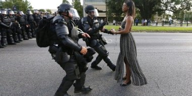 Woman facing riot police