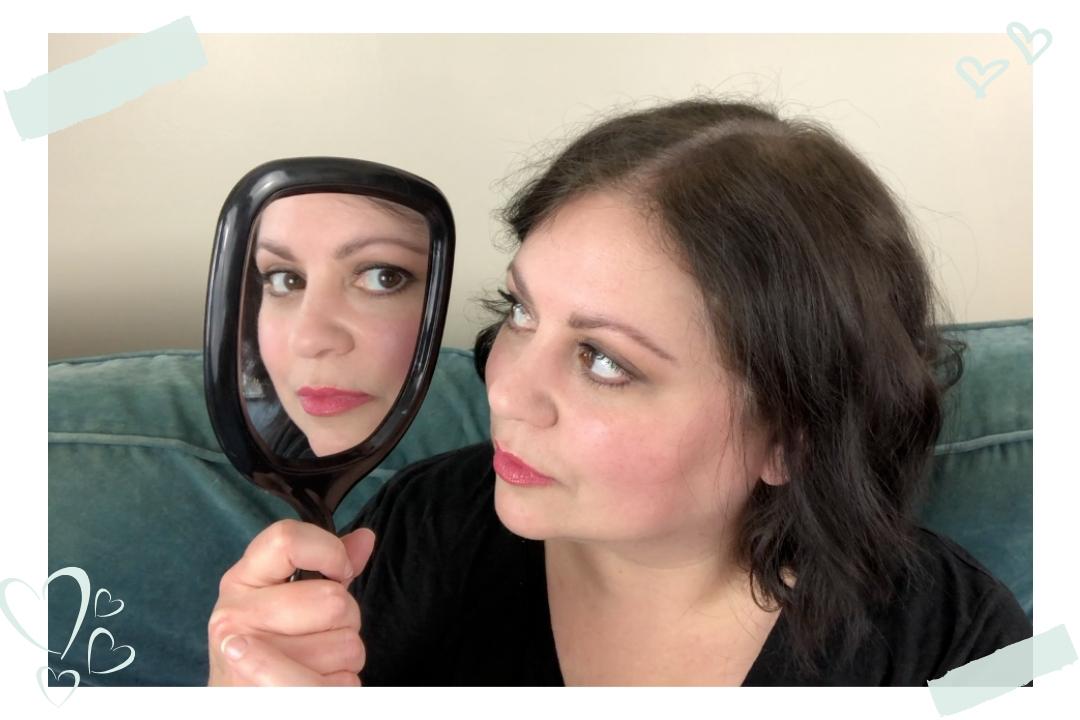 Donna DeRosa holding mirror