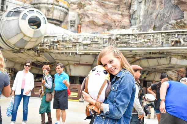 Standing in front of the Millennium Falcon in Galaxy's Edge at Disneyland. I'm sporting my Star Wars Style with my Porg plush backpack, a star and moon hair clips, and my Star Wars denim jacket.
