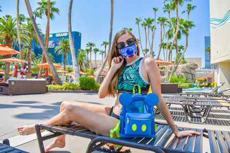 I am lounging poolside at the MGM Grand. I used my rewards to redeem a free stay with MGM Grand specifically to use their pool and lazy river for the day. I am wearing tropical print with my neon blue Mickey Mouse Loungefly backpack, surrounded my palm trees, with the hotel in the background.