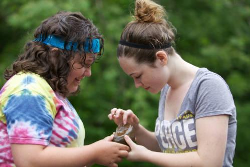 Two teen girls identify a macroinvertebrate