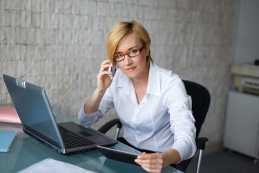 Professional businesswoman calling by cell and using tablet