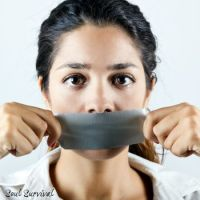 Young woman with mouth covered with tape. Concept of forbidden opinion