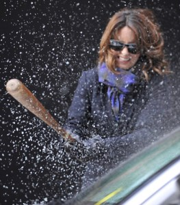 Woman breaking glass with baseball bat