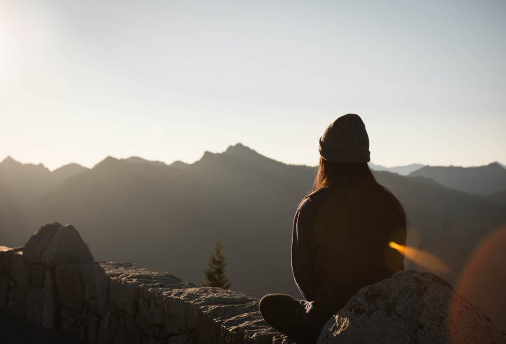 person wearing knit cap facing mountain