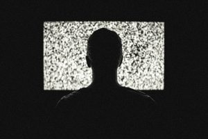 Person in silhouette of tv screen of white noise