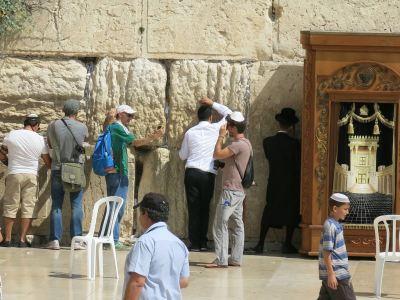 Touching the Western Wall in Jerusalem.