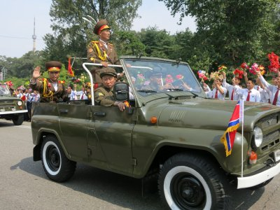 Military vehicles drive past with lots of North Korean army guys, all proudly dressed and happy.