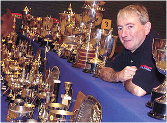Northern Irish motorcycle legend Joey Dunlop with some of his trophies.