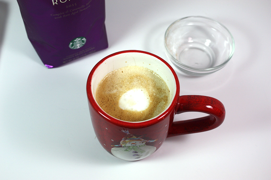 holiday spice flat white in red Christmas mug on white table