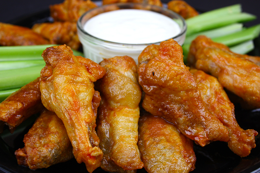 crispy oven baked wings on black tray with celery and blue cheese dip