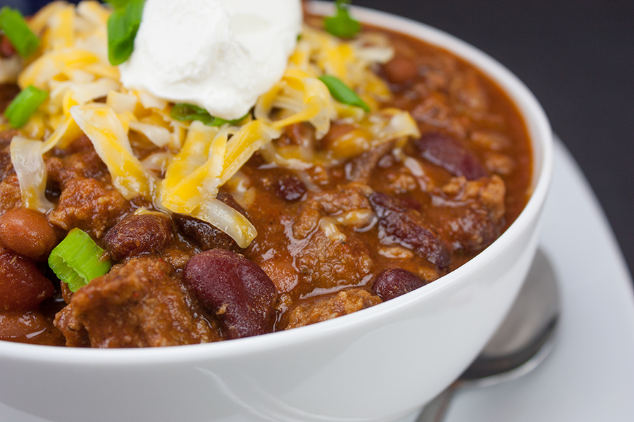 thick chili in white bowl garnished with shredded cheese, green onions and sour cream