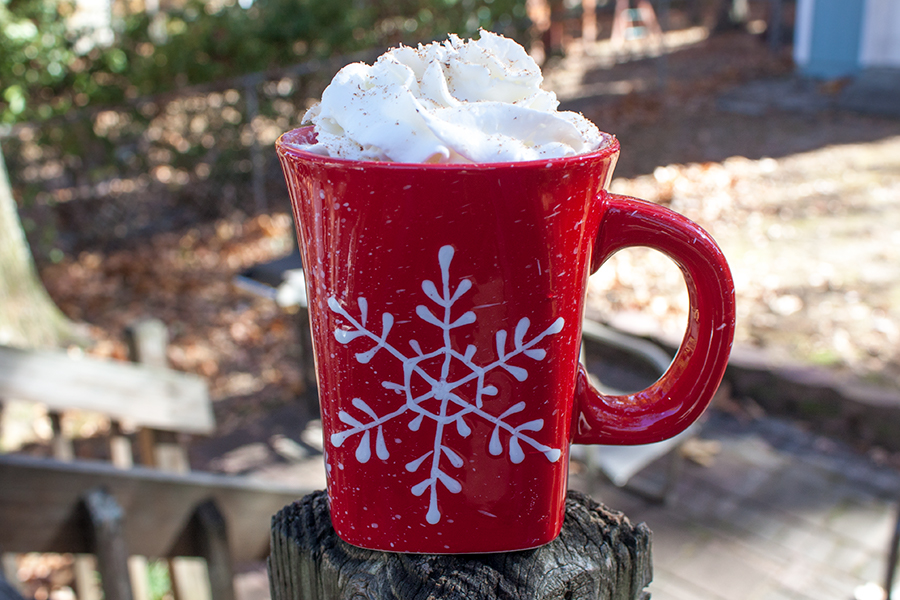 eggnog latte in red coffee mug with snowflake design outdoors on a porch rail