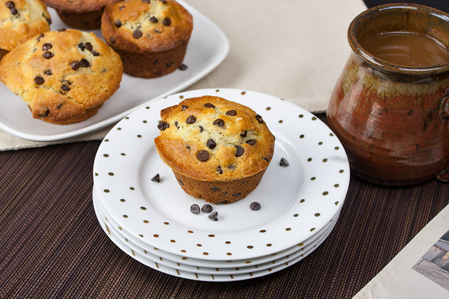 Chocolate Chip Muffin on stack of white plates with gold dots mini chocolate chips on plate
