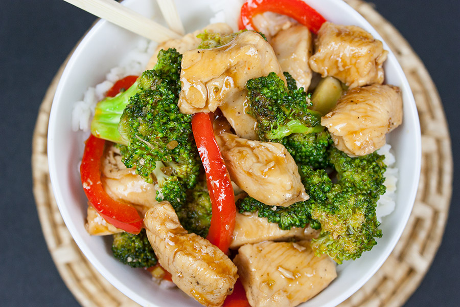 Chicken and Broccoli Stir Fry served over white rice in a white bowl with chop sticks