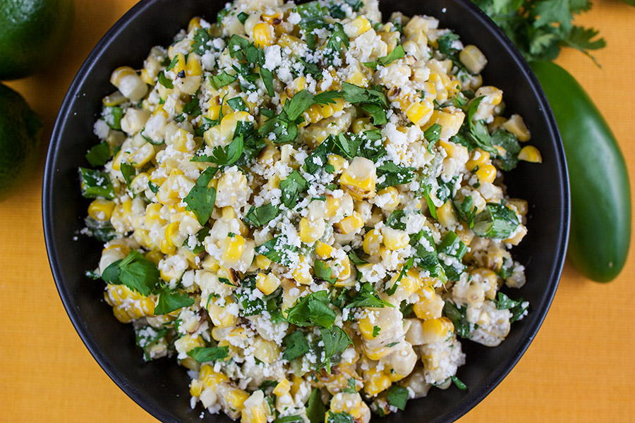 close up of Grilled Mexican Street Corn Salad in black bowl garnished with chopped cilantro