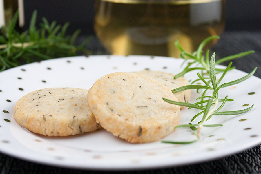 three Parmesan Rosemary Shortbread on white plate with gold dots garnished with fresh rosemary sprig