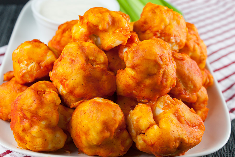 Baked Buffalo Cauliflower Bites on white platter with celery sticks and ranch dip
