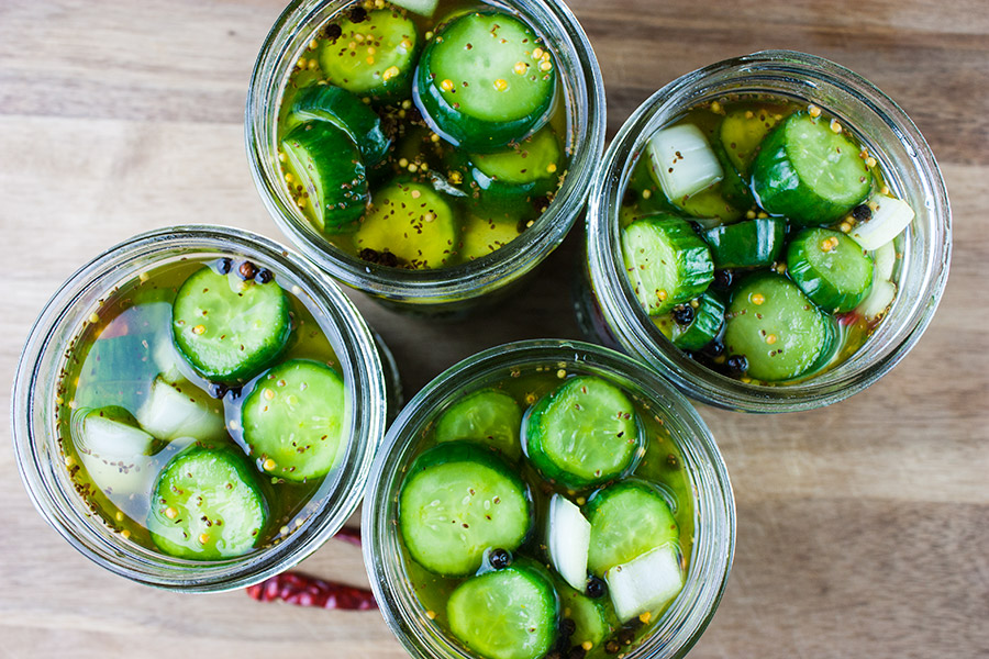 Spicy Bread and Butter Pickles in 4 canning jars on wooden cutting board